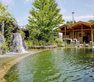 Schwimmteich mit Wasserfall und Poolhaus