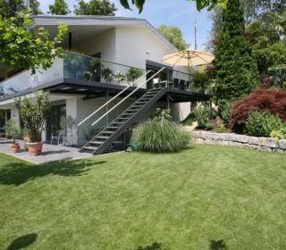 Gepflegter Rasen mit Terrasse und Balkon